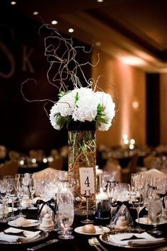 Tall white floral with branches and black ribbon wrap, low floating candles