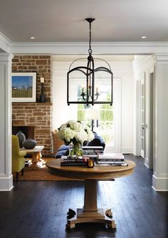Round table in entry, foyer, brick fireplace, dark wood floors