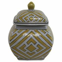 """Add a pop of color to your entryway console or vanity with this lidded ceramic jar, showcasing a geometric pattern in white and gold.   Product: JarConstruction Material: CeramicColor: White and goldFeatures: Geometric patternDimensions: 8"""" H x 6"""" W x 5.5"""" D"""