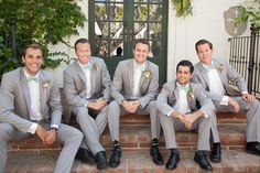 Rustic outdoor wedding at the villa san juan capistrano groom heather grey suit with white dress shirt and mint green bow tie with white and green floral boutonniere with groomsmen heather grey suits with mint green bow ties and black dress shoes sitting down on steps
