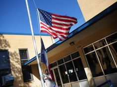 Jerry Arnold lowered the flags in front of H.S. Thompson Elementary School on Bexar Street in South Dallas on Nov. 01, 2011. The school has since closed.