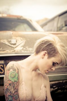Short hair, a tattoo ánd an American musclecar in the background !