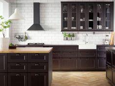 Tradisjonelt mørkt kjøkken i massivt tre og svarte benkeplater samt tradisjonelle hvitevarer