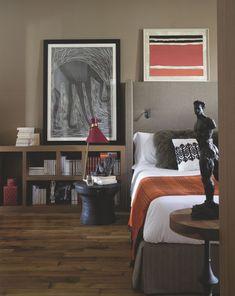 """Sculpture, peinture, couleur... la chambre de ce couple voyageur porte l'empreinte de Domitille : noir sur blanc pimenté de rouge passion. Où que se pose le regard, un personnage sculpté nous interroge. Sur le guéridon, The Conran Shop, nu en terre cuite à patine bronze, et sur le tambour de pluie laotien, Asiatides, sujet masculin assis de dos. À côté, lampe """" Peggy """", Gong. De part et d'autre de la tête de lit en tissu taupe, Manuel Canovas, bibliothèques basses en chêne naturel emplies…"""