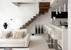 #Contemporary loft space with floating wood #stairs and white #furniture
