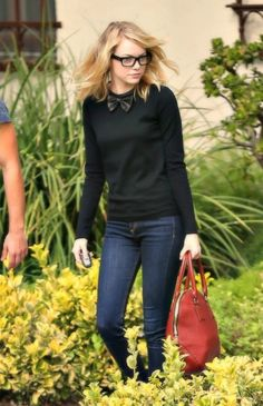 Emma Stone goes geek chic this week, with a nice red handbag to accent her dark look.