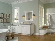 If you've got the room, why not add a little bench just outside the shower room? The perfect spot to perch while getting dressed or putting on shoes, you'll find yourself using it every day. The ability to match cabinetry doors, like with these white beadboard cabinets in our Hawken style, allows the look flow around the corner to the vanity, or even down the hall for total home coordination.