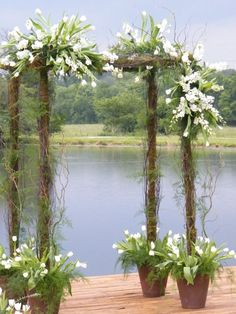 Wedding Floral arbor with sprays of white flowers. It's on a deck facing the water and the beams are placed in heavy plant containers. Great idea for a wedding arbor by the water.