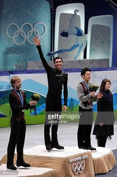 Gold medalist Evan Lysacek of the United States celebrates with silver medalist Evgeni Plushenko of Russia and bronze medalist Daisuke Takahashi of...