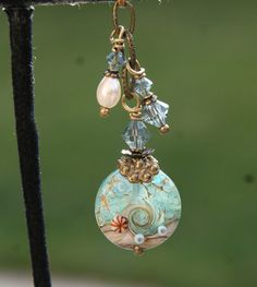Handmade lampwork glass beads complimented with antique brass cap, pearl, and antique brass findings along with a couple of small Swarovski