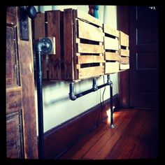 Dresser made from reused apple crates and plumbing pipe. Door are hinged to allow for storage