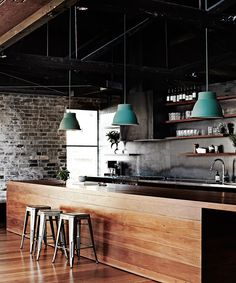 The show-stopping island bench in this [converted Melbourne warehouse](http://www.homestolove.com.au/inside-comedian-merrick-watts-happy-home-3465)  is made from reclaimed ironbark, with the timber also offering a warm contrast to the exposed brick of the original building. Statement pendant lamps finish off the industrial style. Photo: Sharyn Cairns