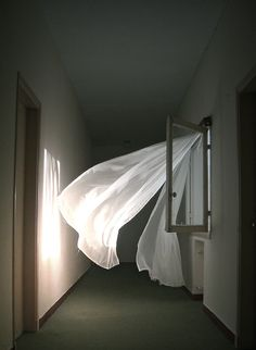 Photo by Bastien Hall. This is dreamy and scary. Lovely white curtains blowing in the wind....in what appears to be a very drab and depressing office or industrial space. Contrasts!