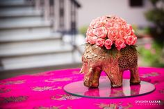 Table decorated with antique rose adorned elephant centerpieces