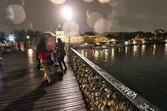 Visitors to the Pont des Arts Bridge on a Rainy Paris Night Examine Padlocks Affixed by Couples as a Symbol of Their Love
