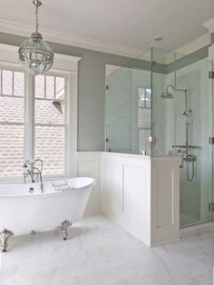 Light fixture, wall color. Airy bathroom with white silver clawfoot bath tub