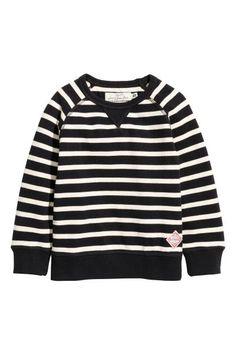 Een sweater van katoenpiqué met lange raglanmouwen en een kleine applicatie onderaan. De sweater heeft een ribboord aan de onderkant en onder aan de mouwen.