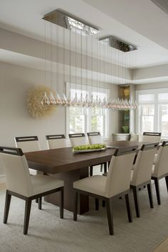Contemporary dining room 14 httphativebeautiful modern this modern dining room space features a long glass chandelier hung over a warm wood dining table adding a touch of elegance to the stark modern space sxxofo