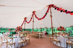 Still swooning over this Sperry Tent look with paper honeycomb garland, white farm tables and vibrant details at a Willowdale Estate summer wedding filled with fun details and color! See more from this event on our website!