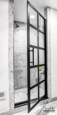 In-fashion master bathroom with an industrial glam interior design intent.   This beautifully designed bath space features brass plumbing fixtures, white Carrara subway tiles, and a factory window style black framed Gridscape Shower Door by Coastal Shower Doors.  #InteriorDesign #HomeDesign #interiorstyle #designchat #designtv #gridscape #showerdesign