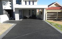 Jet black resin bound aggregate driveway for a modern home