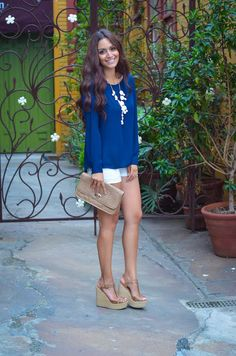 White shorts, blue top, white statement necklace, nude shoes and bag.