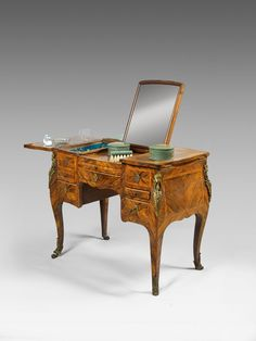 DRESSING woman veneer fronted kingwood and rosewood frame.  It opens with three flaps on the center mounted mirror.  interior discovers two lockers.  In front, it opens with four drawers and a shelf .  Contains containers of Saint Cloud soft porcelain and bottles and glass elements of the eighteenth century.