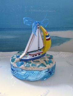 Sailboat Wedding Cake Topper~Beach Glass Cake Topper~ Hi:) A 3 sailboat glides across a calm blue Sea to top the wedding cake of the couple with a passion for sailing! Assorted hues of blue Beach Glass are inlaid in sand~~surrounded by a sequined edging of sparkling waves! A sheer satin bow tops the sailboat~~and a glittery little heart adds a sweet touch to the sail:) This simple, fun design measures 4 in the round~~oh, so perfect to top your wedding cake! Enjoy! Cece