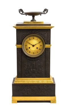 An Empire Style Gilt and Patinated Metal Mantel Clock having a circular engine turned dial with Roman numeral hours, set in a square case, worked to show a lyre, anthemion, rosettes and rinceau scrolls, raised on block feet. Height 21 3/4 inches.