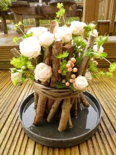 Check out this rather unique bouquet of flowers. White roses are partnered with peach colored berries and bunched together with thin and thick twigs in varying lengths. They are then bound together by a brown rope completing the rustic vice the arrangement gives off.