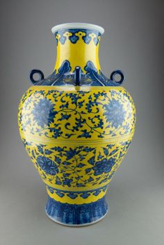 Large Yellow Ground Lotus Vase Qianlong Mark. The baluster form vase with four ring handles on shoulder, richly decorated with lotus and sprigs in blue between two rows of plantain and ruyi on yellow ground, the base marked six characters Qianlong mark. H: 54 cm, D: 34 cm