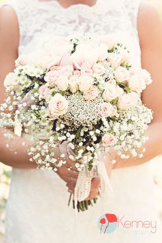What a gorgeous Bridal Bouquet with soft pink roses and baby's breath! Sentimental touch includes a small charm of the Brides Grandmother bound with twine! Photography by: https://www.facebook.com/KenneyPhoto
