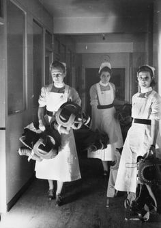 Nurses carry baby respirators along a corridor as part of a gas drill at a London hospital, 1940 ~