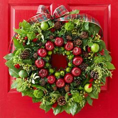 smaller wreath form adorned with apples, Key limes, pinecones, and boxwood fits perfectly inside a larger wreath decorated with limes, lemon leaves, berries, cypress, thistle, and bells of Ireland. To make this festive door decoration