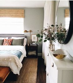 Round mirror, sconces, white bedding with colorful pillows, greenery