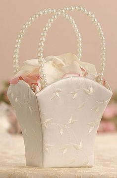 """Standing 8.5"""" tall, this ivory satin flower basket has been embroidered with a lovely leaf and vine pattern.  The handles are made of a chain of ivory beads."""