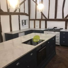 This is the Monaco Carrara in this beautiful barn conversion. It is a completely bespoke worktop due to it having to be sent in oversized so that the fitters could cut down to size onsite due to the walls and beams not being straight and true. What a fantastic job. The kitchen features a u-shape design around the walls with a very large island situated in the middle. A contrast of light and dark colours throughout make it a modern traditional style kitchen.