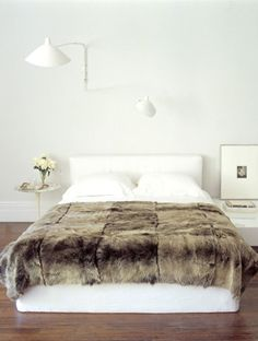 Bedroom by Pamplemousse Design.  Serge Mouille 2-Arm Rotating Sconce, Saarinen 'Tulip' table, white linens + fur throw.
