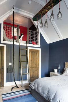 Blue and red boy's bedroom boasts a blue striped rug placed in front of a wood bed dressed in gray bedding lit by linear cage chandelier hung from a white panel vaulted ceiling. Turquoise Teen Bedroom, Bedroom Red, Bedroom Photos, Bedroom Loft, Bedroom Decor, Bedroom Themes, Bedroom Apartment, Vaulted Ceiling Bedroom, Teen Bedroom Designs