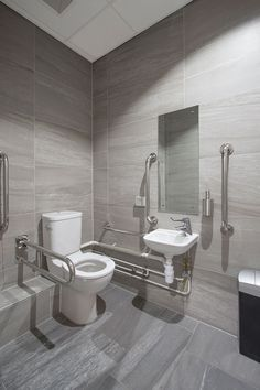 A commercial office disabled toilet, featuring wall and floor tiles from Solus Ceramics. Two shades were selected from the marble inspired Rawstone range.