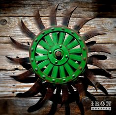 """Stunning old wheel with curved spikes and luscious remnants of original green paint!Heavy duty bracket projects the wheel 3"""" from the wall, allowing it to spin and create a dazzling effect with light and shadow! See video at http://youtu.be/Dh9pZ_UHLRg19"""" diameter.Special order! Please allow 2 weeks for crafting."""
