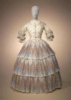 Two-piece dress of white cotton batiste, printed with bloemetjes-, spring, and zigzag motifs consisting of bodice and skirt with wide flounces....circa 1855