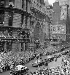 New York's financial district teems with people as Gen. Dwight D. Eisenhower was welcomed at Manhattan's lower Broadway and Vesey Street on June 19, 1945, after the conclusion of the war in Europe. Seated in the back seat of the same car is New York Mayor Fiorello LaGuardia.