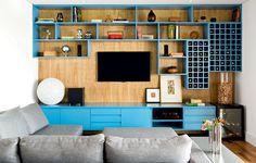 A designer de interiores Magda Marconi criou uma estante com nichos de tamanhos variados e com acabamento de laca azul, fixados no painel de freijó sarrafeado, onde a televisão foi fixada. A execução é da Japy Marcenaria