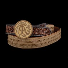 """Lozano created a flat panel of braided rawhide 86-strands in width while Pedro Pedrini fashioned the hand-carved leather billet for this gentleman's belt, size 42. The flat elements reflect the use of the traditional Trenza Patria braiding in 8-, 14- and 18-strands laced together on the backside. The centerpiece is 18-plait flanked by 8-plait braid twisted into an """"S"""" pattern. The round-rawhide covered buckle features a braided edge and rawhide stitched TCAA logo. $7468"""