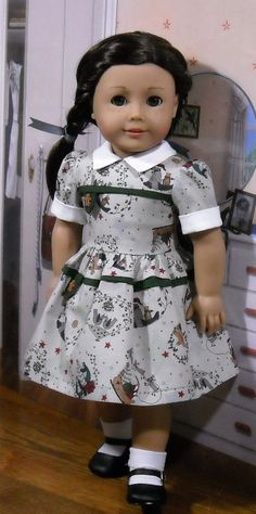 Your favorite girl will be all set for winter holidays in this classic dress done in a gray, green and red cotton print with dark green