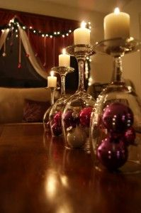 up-side-down wine glasses with ornaments and topped with candles