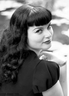1950s hairstyle with loose curls and bangs