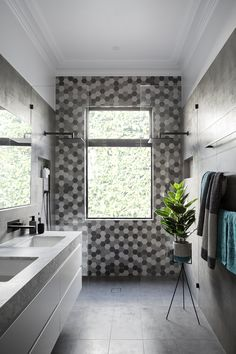 In this modern bathroom, the grey and white double vanity provides ample space for two people to get ready in the mornings, and the grey wall tiles match those on the floor and compliment the hexagon tiles on the wall in the two-person shower.