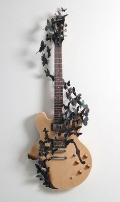 I love how an ordinary object was turned into art! The simple colors of the wood and metal give insight into the flowing forms and dramatic effect. To me, the butterflies imply the movement of music that comes from the strings of a guitar.